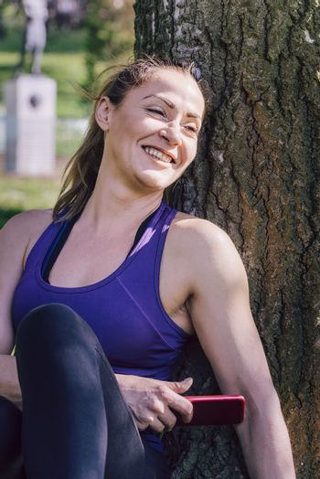 sporty woman resting after exercise to take a look to her phone while sitting next to a tree, healthy modern lifestyle and sport concept