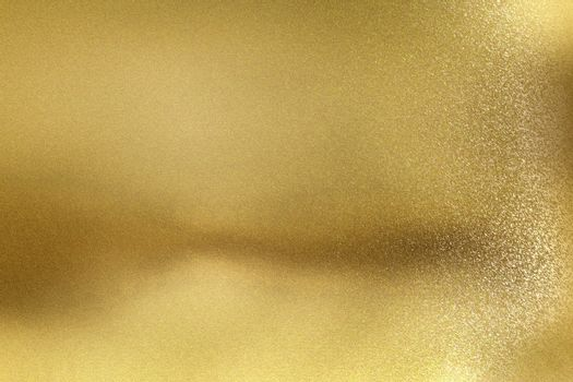 Glowing golden metal wall with scratched surface, abstract texture background