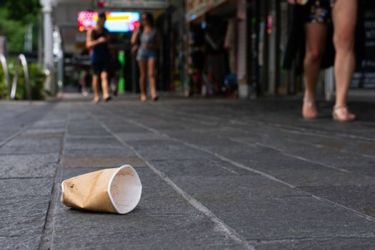 Disposable cup littered on sidewalk