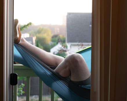 Boy laying in hammock in apartment in city