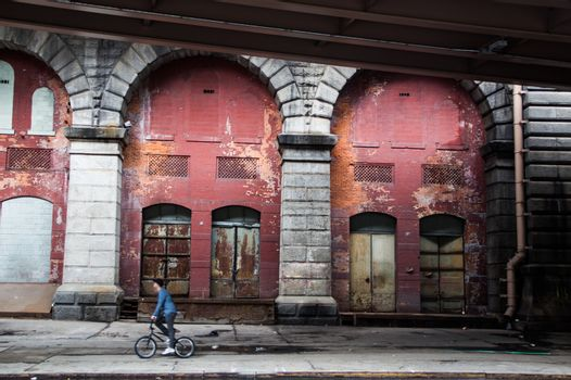 Man biking under the bridge in the city with an old fashioned exterior