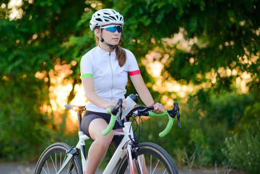 Portrait of Young Woman Cyclist Resting with Road Bicycle at Sunset. Sport and Healthy Lifestyle Concept.