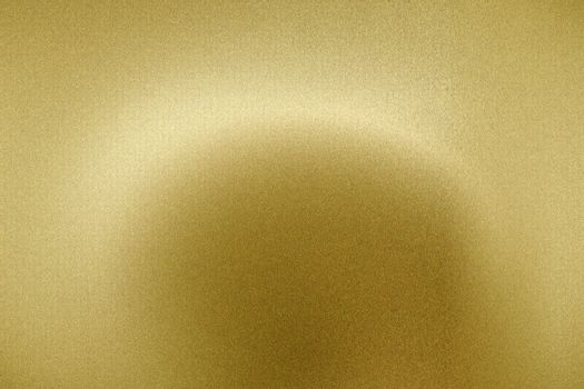 Light shining on brushed gold metal panel, abstract texture background