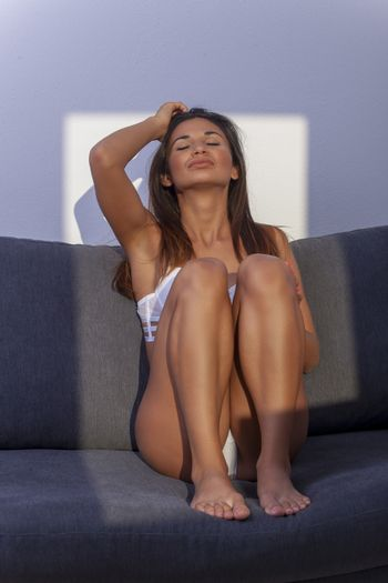 brunette woman sitting on a couch