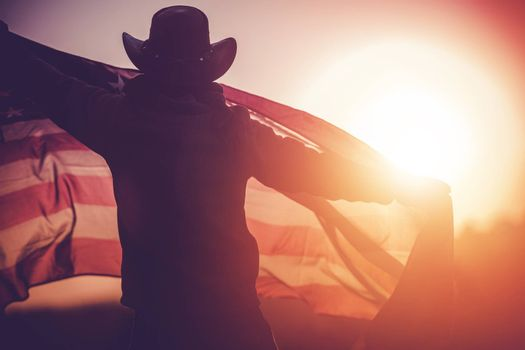 Independence Day Celebration. Western Wear Men in Cowboy Hat with United States of American Flag Celebrating 4th of July.