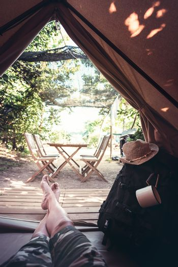 vertical view of crossed legs of a hiker man resting barefoot in a camping tent, travel discovery concept, point of view shot
