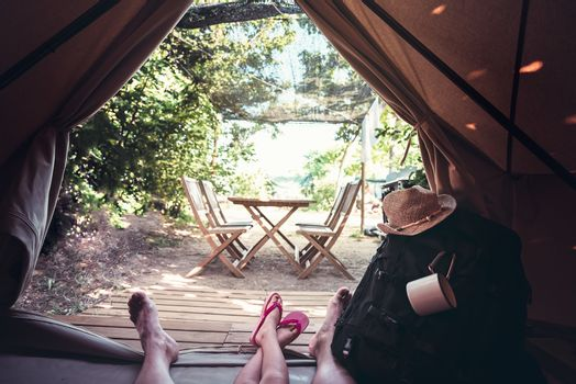 view of the legs of a hiker man with a kid resting barefoot in a camping tent, travel discovery concept, point of view shot