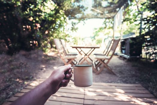 view of a hand of a hiker person resting with a cup in a camping, travel discovery concept, point of view shot
