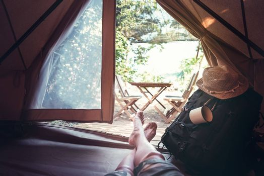 view of crossed feet of a hiker man resting barefoot in a camping tent, travel discovery concept, point of view shot