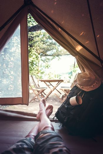 vertical view of crossed feet of a hiker man resting barefoot in a camping tent, travel discovery concept, point of view shot