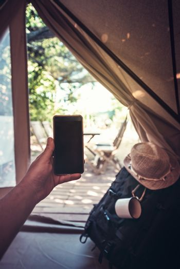 vertical view of a hand of a hiker person resting while consulting the phone in a camping tent, travel discovery concept, point of view shot