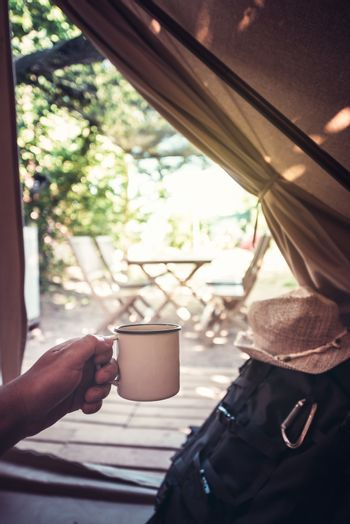 vertical view of a hand of a hiker man resting with a cup in a camping tent, travel discovery concept, point of view shot