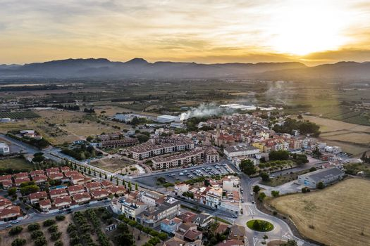 top view of Vinyols i Archs village, Baix Camp, at sunset near of the mountains in Tarragona, next to fields and agriculture industry, aerial view