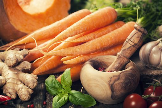 Healthy food cooking background. Vegetable ingredients. Fresh garden carrots, onions, pumpkins, ginger and spices on rustic wooden background