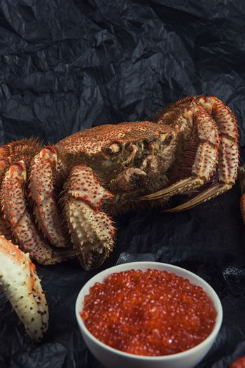 Closeup of of hairy crab with plate of red caviar