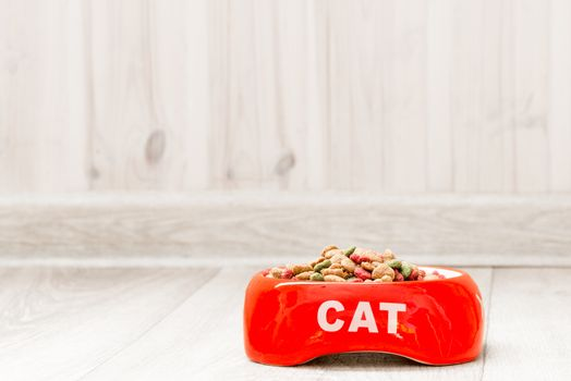 Red bowl for a cat with dry food on the floor in the house close-up