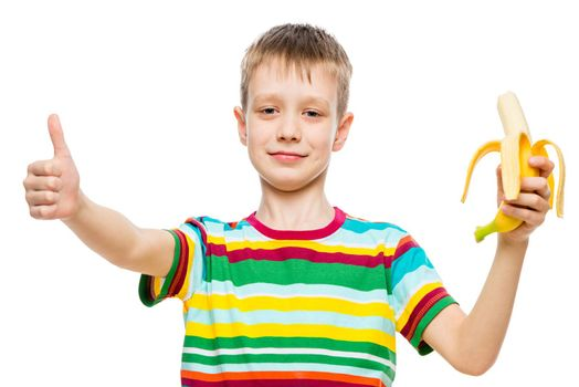 Portrait of a happy boy on a white background with a banana in his hand isolated