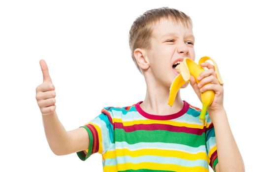 Happy boy eats tasty banana on white background, portrait is isolated