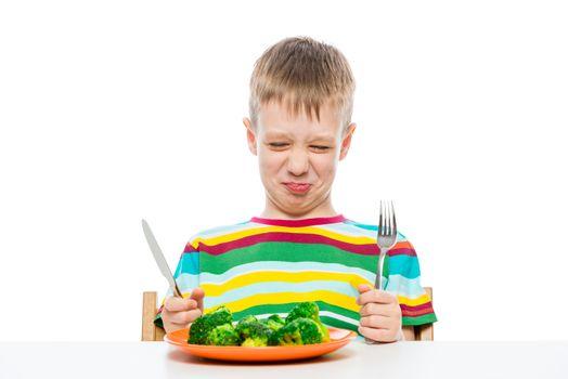 Grimace of a boy who does not like broccoli, portrait on a white background