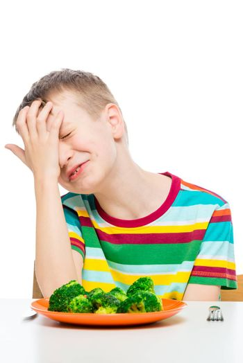 sad boy does not want to eat broccoli, a portrait with a plate on a white background