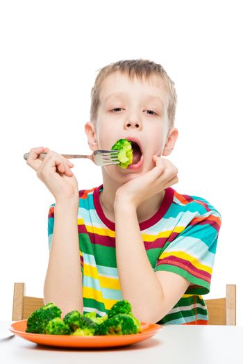 Vertical portrait of a boy who has a diet food, a child eats broccoli on a white background
