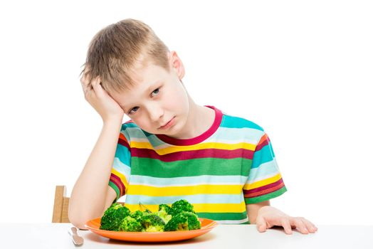 Sad child with a plate of broccoli at the table, portrait isolated