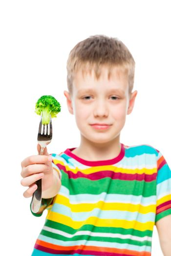 Vertical portrait of a boy with broccoli on a fork, vegetable in focus