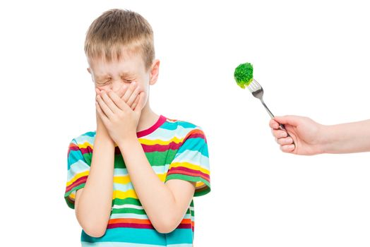 boy refuses serving healthy broccoli, emotional portrait of a child isolated on white background