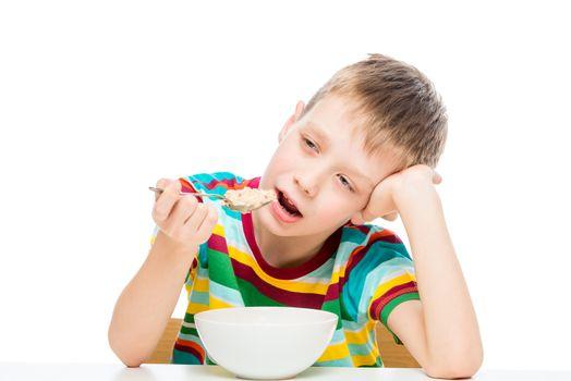 boy eating porridge, portrait of a child isolated on white background