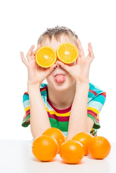 humorous photo of a boy with oranges halves on a white backgroun