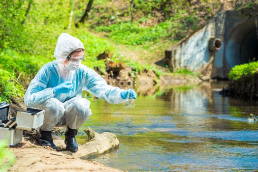 Environmental scientist with a flask takes a sample of water at the site of industrial discharge of water