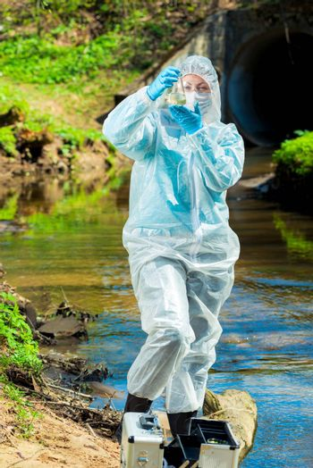 dangerous sewer water, a scientist takes a sample of water in protective clothing