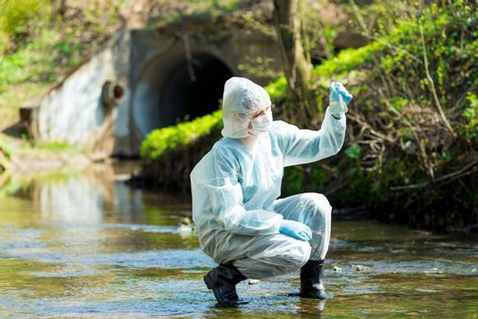 a scientist with a test tube takes a sample of water from a sewer discharge