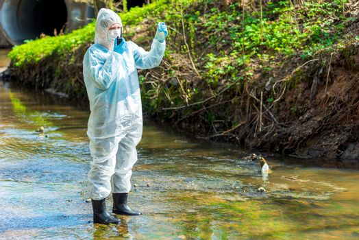 a scientist with a sample of contaminated contaminated water with a walkie-talkie warns about environmental castrophy