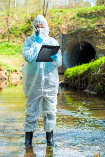a female scientist with a walkie-talkie and a notebook fixes environmental disasters in the river