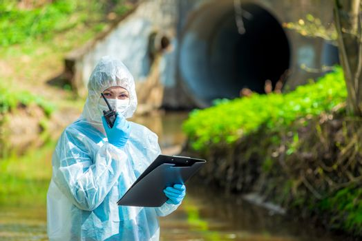 a scientist with a walkie-talkie on the background of a sewer pipe