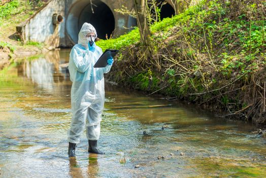 portrait of a scientist in sewer water with a walkie-talkie