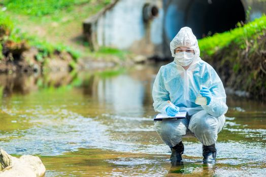 researcher scientist in protective clothing on the nature of conducting research on water