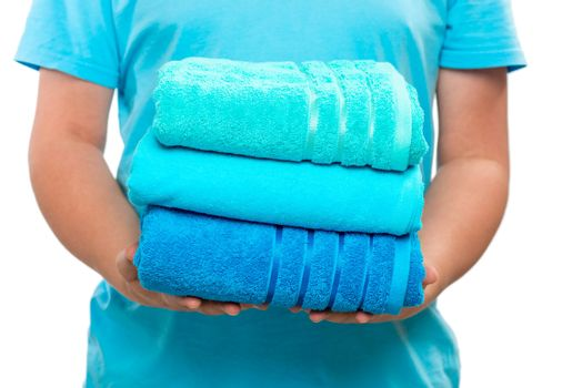 stack of ironed terry towels in male hands close-up