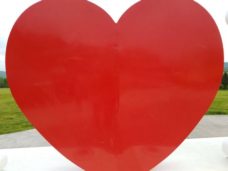 large red heart curved shape outdoor with green grass