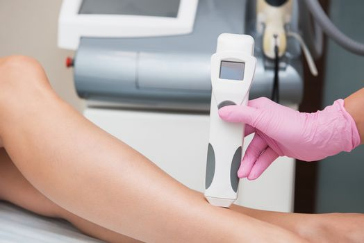 Specialist makes skin tone measurements on a womans leg, to determine the settings for hair laser depilation. First step before depilation. Cosmetology and SPA concept