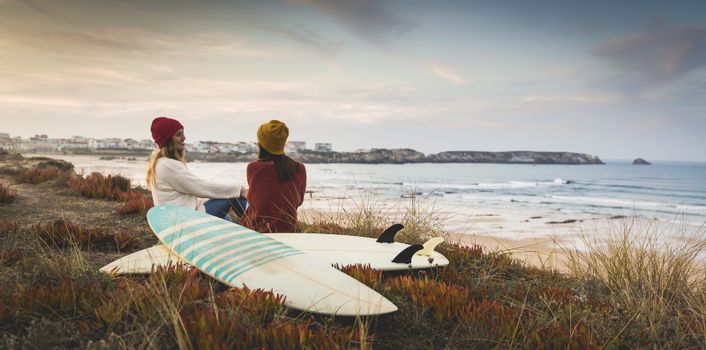 Two best friends sitting near the coastline with her surfboards while looking to the ocean