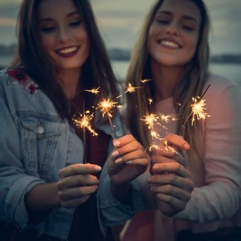 Two best friends celebrating, holding sparklers at beach