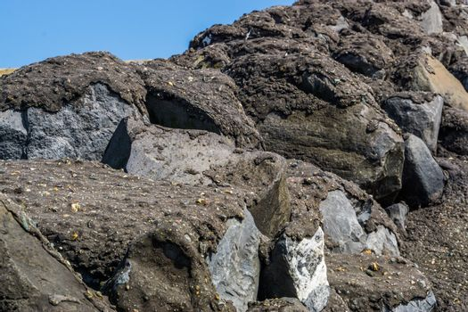 big rocks covered in black tar, Architecture background, Closeup boulders