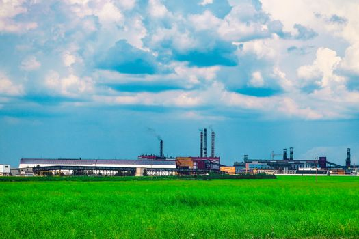 Fumes of a mining plant against the sky and green grass.