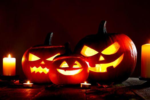 Halloween pumpkin head jack o lantern and candles on gray background