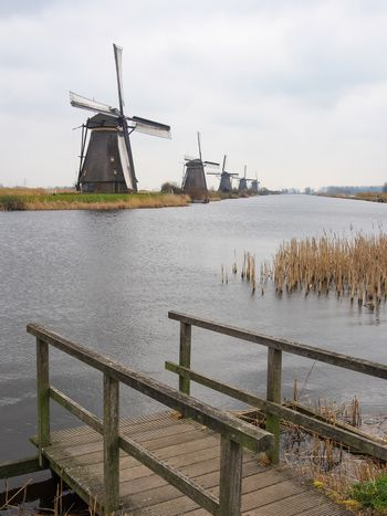 Netherlands rural landscape with windmills and canal at famous tourist site Kinderdijk in Holland