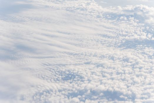Unreal and dramatic Altocumulus cloud formation at sunrise from airplane