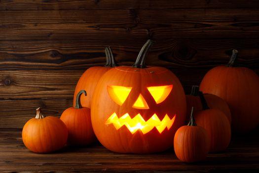 Glowing Halloween pumpkin heads jack o lantern on wooden background