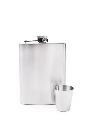 Stainless steel flask with a small metal cup, placed next to each other, isolated on white background.